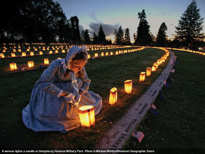 A woman lights a candle at Gettysburg National Military Park