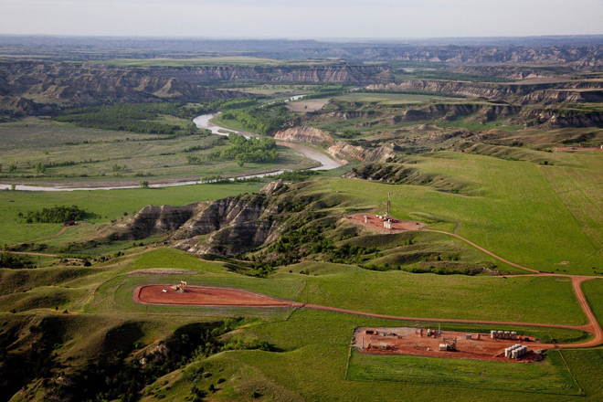 """These three wells sit atop a cliff overlooking the Elkhorn Ranch Unit of the park (above the """"s"""" curve in the Little Missouri River in the background) where Theodore Roosevelt operated a cattle ranch in the 1880s. The development is visible from the park."""