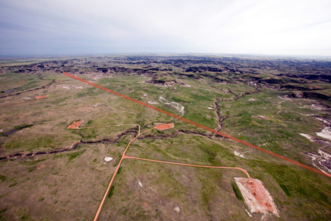 Six well pads are visible in this aerial shot, immediately adjacent to the northeast boundary of the South Unit of Theodore Roosevelt National Park. The park boundary (shown here in orange) runs diagonally from the upper left to lower right of the image, just beyond the well pads.