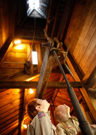 Two Boy Scouts peer to top of the derrick in enginehouse at Drake Well Museum. Photo © Heather Mull.